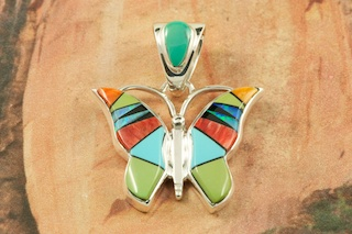 Stunning Butterfly Pendant featuring Genuine Sleeping Beauty Turquoise, Nevada Turquoise, Spiny Oyster Shell and Black Jade inlaid in Sterling Silver. Beautiful Fire and Ice Lab Opal Accents. Free 18&quot; Sterling Silver Chain with Purchase of Pendant. Designed by Navajo Artist Calvin Begay. Signed by the artist.